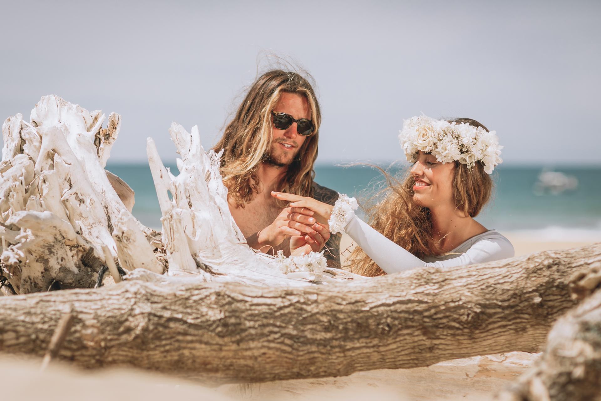 """Una boda surfera en una duna, cerca del mar, descalzos, sin corbata, sin ataduras , con el vestido mas bonito soñado, libres ,sin anillos , solo unas pulseras de flores naturales una diadema como único adorno , sin apenas maquillaje y como única invitada la naturaleza y así felices con la tabla de surf ,correr al agua de la mano. Ir juntos al mar, hasta el infinito ... que mejor forma de empezar una vida juntos.[su_spacer size=""""40""""] Esa boda que alguna vez todos hemos soñado, los amantes del surf y los que no lo son tanto, seguro que disfrutaran viendo este reportaje en la Landas.    [su_spacer size=""""40""""] Han sido muchos los que han querido participar en este inspiracional y queremos darles las gracias a todos,porque sin ellos estas fotos no hubieran sido posibles. En primer lugar, queremos dar las gracias a nuestros modelos Irene Arrospide y Mikel Yanci , fue genial conoceros y pasar el día con vosotros. Asi como a Reina de Bodas,que nos ayudó con la decoración de la mesa. Los colaboradores son; Yolanda Torres como diseñadora del precioso vestido que llevaba Irene Arrospide; Olazt de la Floristeria Baigorri que además de las flores, diseñó la increible diadema de flores liofilizadas de la modelo y las pulseras de flores que se intercambiaron los modelos a modo de anillos, en nuestra peculiar ceremonia. La tienda Milako, que se encargó del outfit del novio con una original americana. Nuria de N Concept creadora de la marca Kionita que también quiso participar dejándonos dos de sus espectaculares diseños de bañador y biquini ,que le quedaban a la modelo increibles. Contamos con los muebles de Studio Bastiaan,os animamos a conocer sus creaciones y con las creaciones de gafas Kabo ,os encantarán.Y por último, pero no menos importante agradecer a nuestros amigos Ruben Crespo y Amaia por ayudarnos con todo este proyecto. Gracias por grabar el video y cargar con las sillas tablas ,flores etc sin ti, Amaita habría sido imposible."""